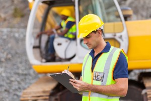 An inspector checks off worker safety protocols